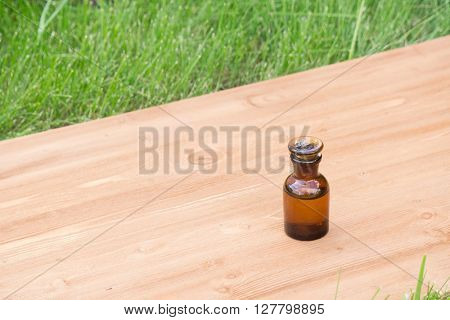 little brown bottle on booden board and grass