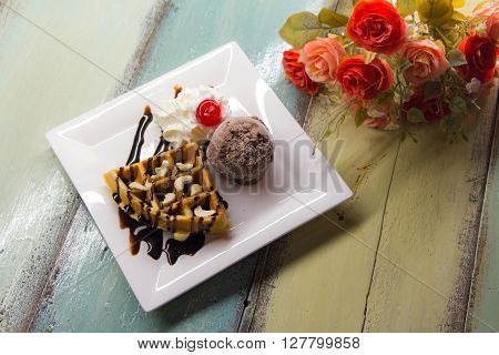 Sweet waffles with chocolate sauce and ice cream chocolate on color wood table