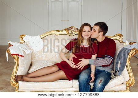 Family portrait - a pregnant woman lies on the lap of her husband, The husband and wife, lovers dressed in a Burgundy style. Beautiful interior