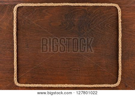Frame of rope lies on a background of a wooden surface with place for your text