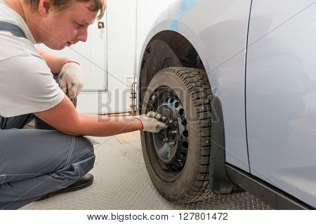 Man Tightening The Screws On The Wheel Of The Car