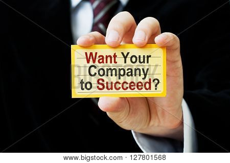 Want Your Company to Succeed. Businessman holding a card with a message text written on it