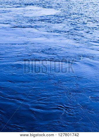 the surface of a beautiful clear blue water that is flowing and bubbling and splashing