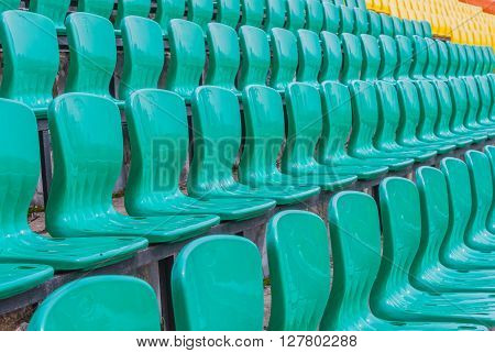 Ranks Colour plastic armchairs on stadium tribune in the open air
