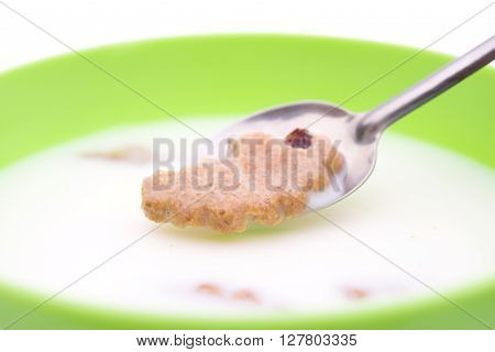 spoon taking out a soaking cracker from bowl of milk