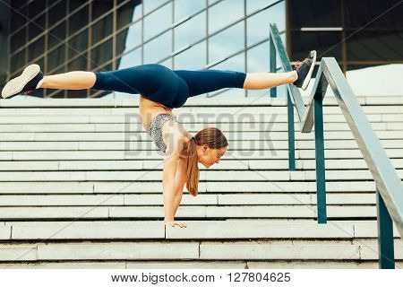 Young woman handstand yoga pose outdoor on the stairs