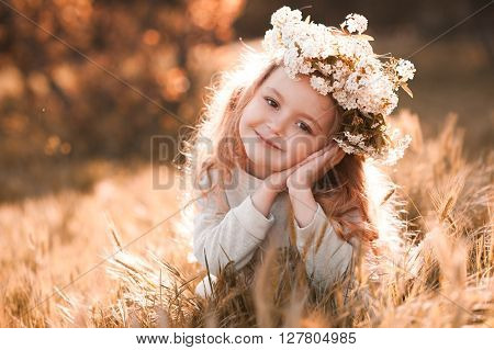 Smiling baby girl 3-4 year old wearing flower wreath outdoors. Sitting in meadow. Looking at camera. Childhood.