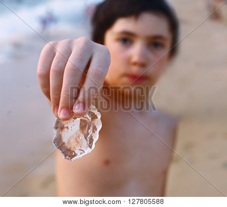 preteen handsome boy look through jellyfish on the seaside beach background close up photo