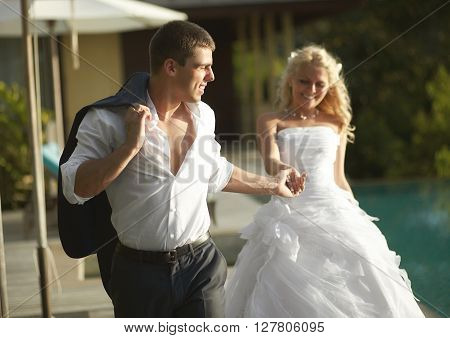 Lovely Bride And Groom Coming Across Pool Area After Wedding.