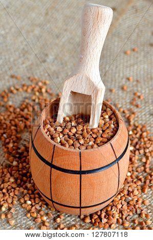 Buckwheat groats, wooden spoon, small wooden barrel on burlap