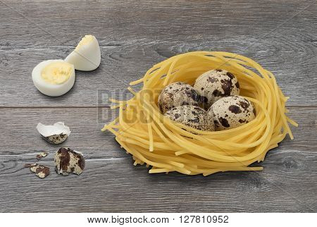 Quail eggs in nest made of pasta on a wooden table. Shelled and unshelled eggs egg shell and pasta.