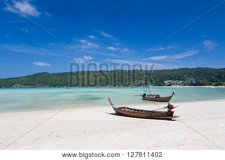 Long tail boat Sits on the beach with mountain background, South of Thailand, natural landscape