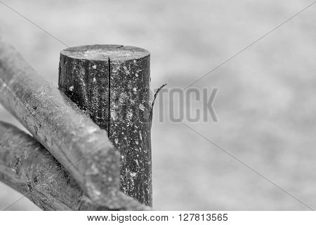 part of an old column from a wooden fence for the ranch closeup on an indistinct background of monochrome tone