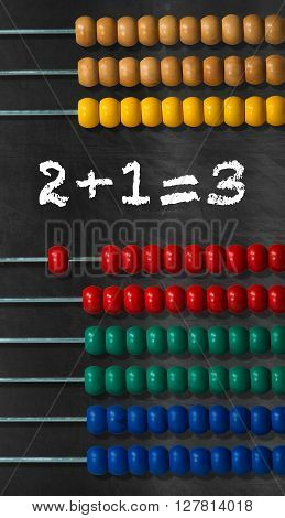 Detail of a wooden and colorful abacus on a black background with a simple math addition
