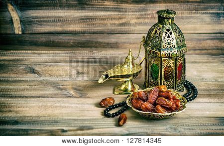 Arabian lantern dates and rosary. Islamic holidays concept. Vintage style toned picture. Vibrant colors