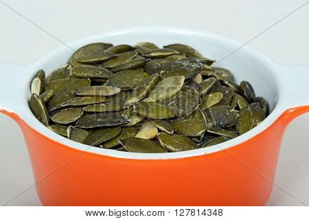 Raw pumpkin seeds in an orange ramekin dish.
