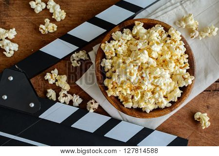 Movie clapper and popcorn on wooden background