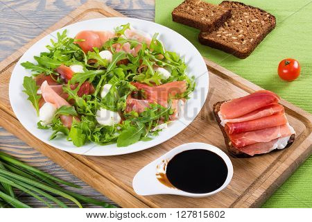 Sandwich with prosciutto and rye bread on a cutting board mozzarella arugula salad on a white dish with balsamic vinegar in a gravy boat close-up