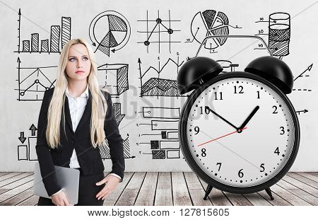 Lack of time concept with thoughtful businesswoman huge alarm clock on wooden floor and concrete wall with business sketches in the background
