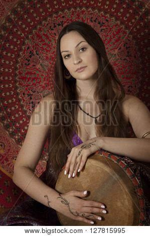 Young adult woman playing drum during meditation session