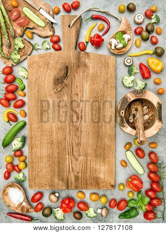 Fresh vegetables and wooden cutting board on kitchen table. Healthy clean food concept