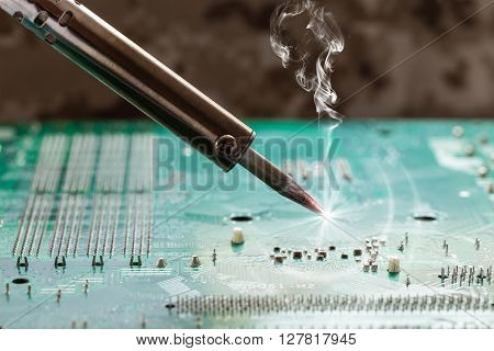 smoking soldering iron on a computer motherboard closeup