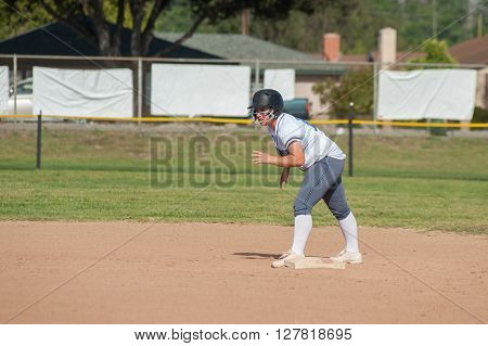 White uniform softball player on second base and ready to run.