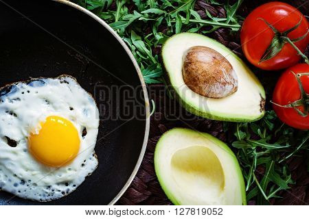 Healthy breakfast: sunny side up egg in iron skillet, halved avocado, tomatoes on vine and arugula salad. Above view
