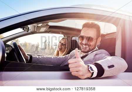 Young man and woman smile at the camera while seated in a new convertible car.Couple buying a car.