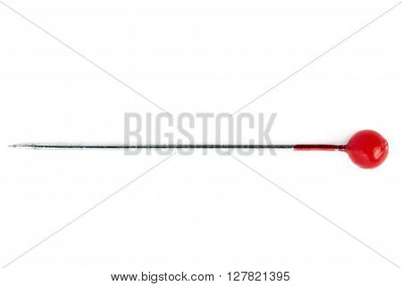 Small sewing push pin needle with red head isolated over the white background