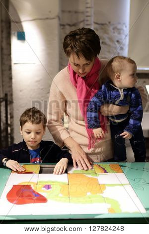 Family playing with puzzle in a museum