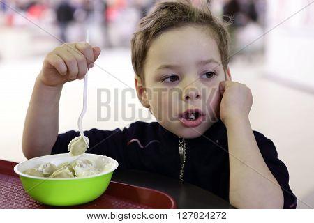 Pensive boy eating meat dumplings in the cafe