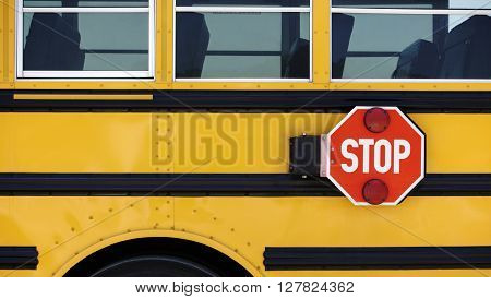 Details of a School bus with a attached Stop sign.