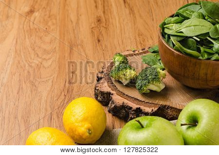 Spring spinach leaves in the bowl broccoli lemons and apples on wooden table background