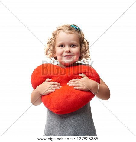 Young little girl with curly hair and red plush heart in gray dress standing over isolated white background