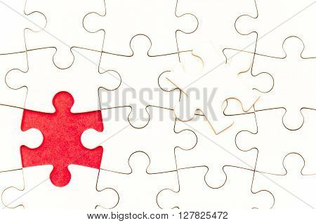 still life with a white jigsaw/puzzle incomplete over a red background the last piece is over the other one symbol of problem solving