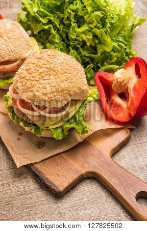 Two homemade vegetarian burgers with fresh organic vegetables on rustic wooden background. Top view with copy space.