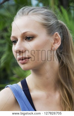 Portrait of beautiful young woman looking at you against green background. Outdoor