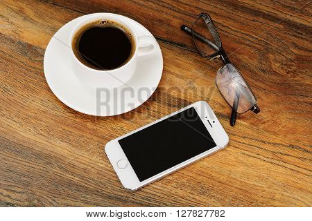 Minsk, Belarus - April 16, 2016: Apple iPhone 5S on Wood with coffee and glasses. The operating system iOS 9. The founders of the company: Steve Jobs, Ronald Wayne, Steve Wozniak.