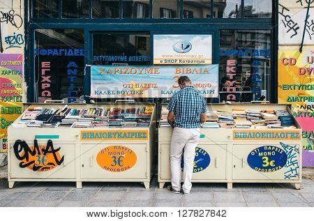 THESSALONIKI, GREECE - MAY 27, 2015: Man chooses a book in a bookshop. Books exhibited in the street.