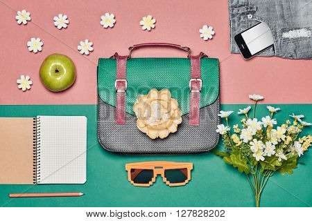 Overhead outfit Fashion ladies set, accessories. Creative hipster look, pastel colors. Handbag, shorts sunglasses, smartphone, apple and flowers. Unusual essentials.Top view, pink green background