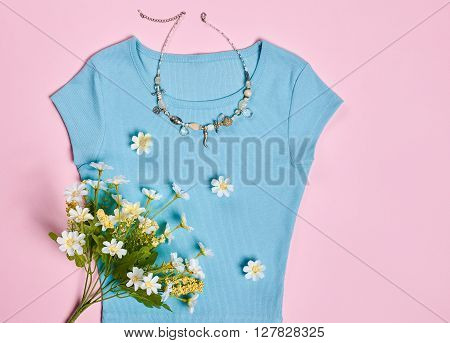 Overhead outfit Fashion girl, clothes accessories set. Glamor creative  blue dress, flowers, necklace, bouquet of camomile. Unusual modern elegant essentials. Top view, pink background