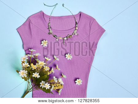 Overhead outfit Fashion woman, clothes accessories set. Glamor creative purple dress, flowers, necklace, bouquet of camomile. Unusual modern elegant essentials. Top view, blue background