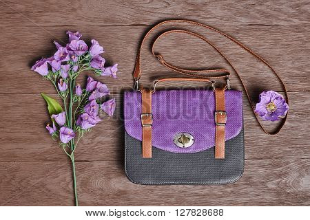 Overhead outfit Fashion ladies accessories. Glamor creative hipster look, pastel colors. Stylish handbag, bouquet of purple flowers. Unusual modern summer essentials.Top view on wood, vintage
