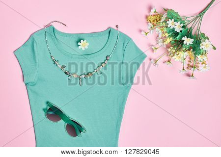 Overhead outfit Fashion Ladies, accessories. Glamor creative  T-shirt, flowers, necklace, sunglasses, bouquet of camomile. Unusual modern elegant essentials.Top view, pink background