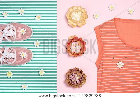 Overhead outfit Fashion girl clothes set, accessories. Creative hipster look, pastel colors. Stylish gumshoes, t-shirt, flowers. Unusual modern summer essentials.Top view, green background