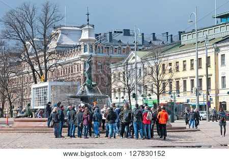HELSINKI, FINLAND - APRIL 23, 2016: Excursion group near Havis Amanda Fountain by Ville Vallgren. Havis Amanda is the symbol of Helsinki. Located between Esplanade and Market Square