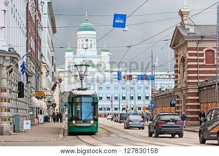 HELSINKI, FINLAND - APRIL 23, 2016: Tram rides not far from The Market Square near Wanha Kauppahalli (The Old Market Hall). On the background is The City Cathedral