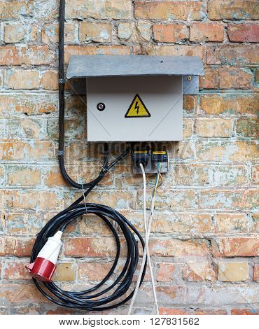 Outdoor Electric control cabinet for electrical equipment on brick wall with wires and plug jack. Knife switch on old dirty wall