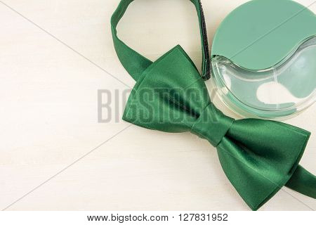 Green Bow Tie And Parfume  On A Table